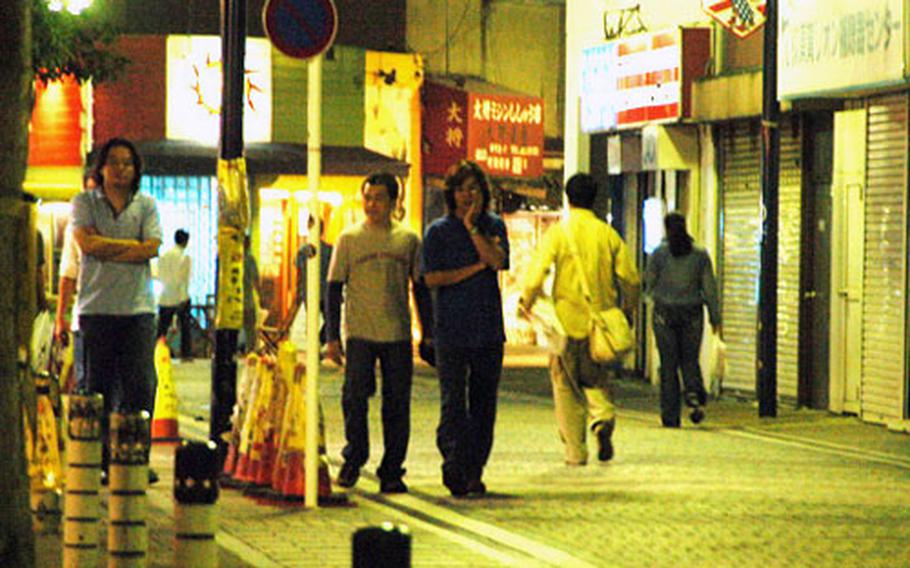People take a late-night stroll through the Honch, the nighttime entertainment district just outside Yokosuka Naval Base, Japan.