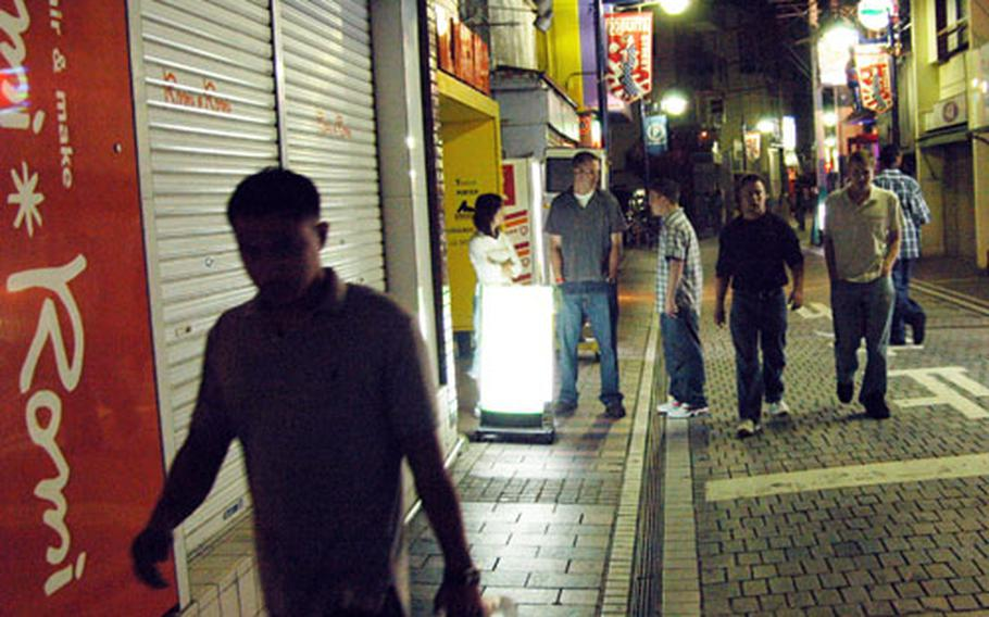 Foreigners talk to a woman outside of a Honch massage parlor in Yokosuka, Japan.