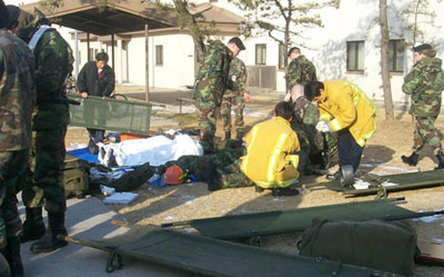 Soldiers and firefighters at Camp Humphreys in South Korea practice treating mock casualties during a mass casualty exercise in Feb. 2005.