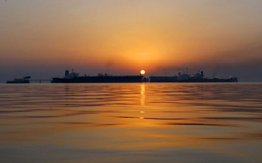The sun sets behind the Basra oil terminal in the northern Persian Gulf.
