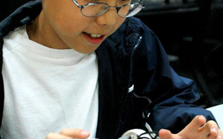 Max Kim plays with a robot during a meeting of the Camp Zama Lego Robotic Club.