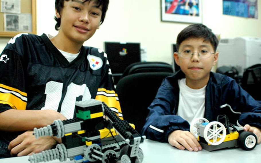 Eric Tankm, left, and Max Kim show off two of the Camp Zama Lego Robotic Club's robots. Both have been members of the club for almost two years.