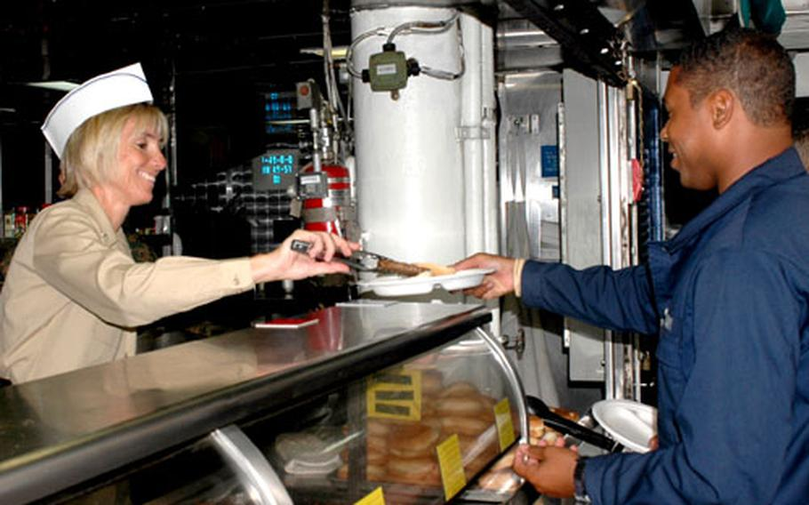 USS Boxer's Supply Officer Cmdr. Beth Howell serves lunch to sailors and Marines on Sept. 28. Howell wanted to show her support for the supply division and her enthusiasm for the ship's innovative 24-hour food service which allow Boxer crewmembers to get meals at any time.