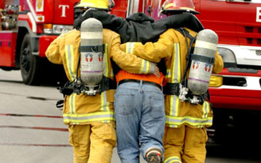 Firemen help a mock victim reach a safety point after a simulated explosion at Camp Humphreys.