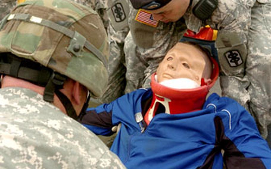 Medical corpsmen load a mock casualty aboard an ambulance prior to transport to the Camp Humphreys troop medical clinic.