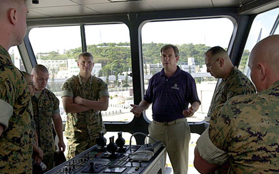 After a ceremony marking the fifth anniversary of WestPac Express' support of III Marine Expeditionary Force, Karl Keller, second mate in navigation, explains the capabilities of the mooring station on the bridge while the high-speed vessel was moored at Naha Military Port on Monday.
