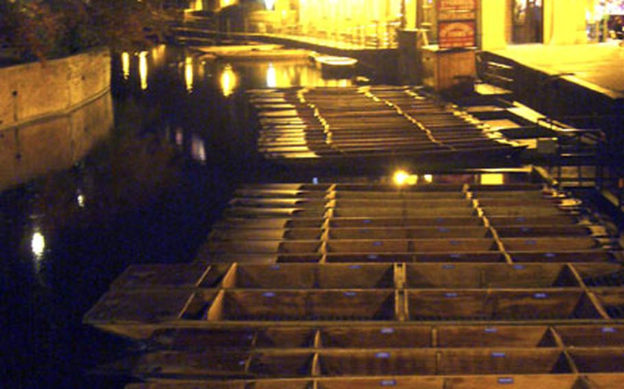 Flat-bottomed boats called punts sit along the River Cam on a recent night.