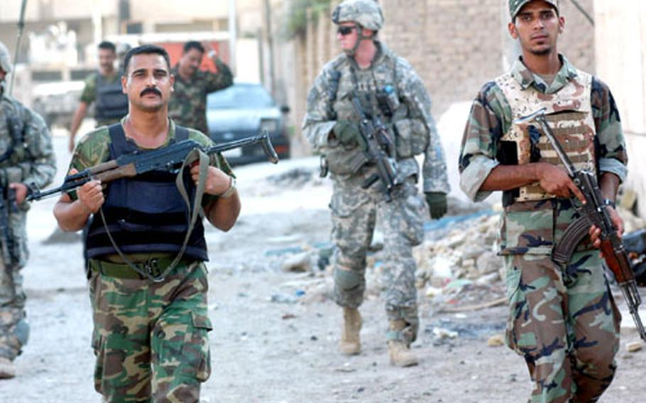 Iraqi National Police members walk through an alley in Samarra, Iraq, on a joint patrol with U.S. forces from Patrol Base Olson on the edge of the city.
