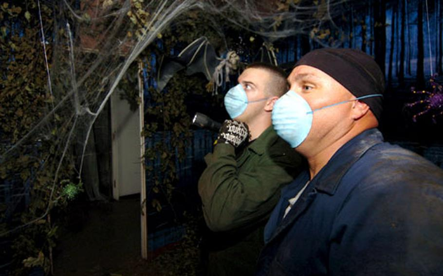 Master Sgt. Scott Samdahl and Staff Sgt. Phil Lorensen check lighting and electricity at the Yokota haunted house.