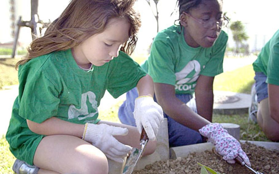 """Lyndze Ward, 9, left, and Allegra Mosley, 11, both with Junior Girl Scout Troop 457, plant flowers in a bed at Kinser Elementary School on Camp Kinser on Tuesday. Mosley said she was proud to work on the project because """"it looked really messy before."""""""