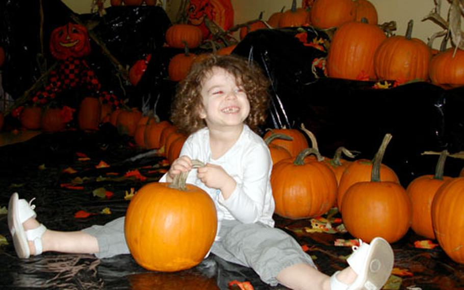 Chloe Demerritt, 3, smiles after having chosen a pumpkin to carve from the Gaeta, Italy, MWR Pumpkin Patch on Wednesday.