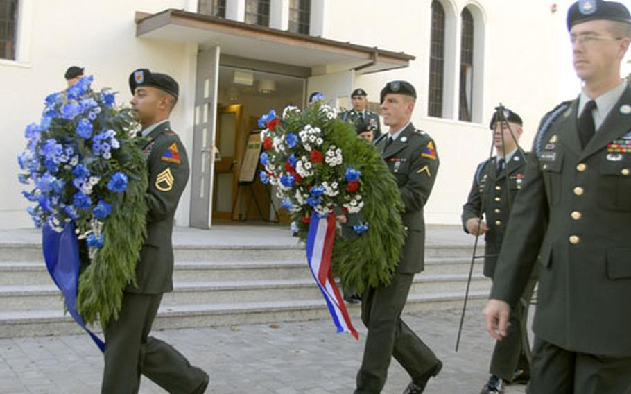 Staff Sgt. Oscar Medina and Pvt. James Gibson, led by Staff Sgt. Nathan Holgrewe, carry wreaths to a monument after a memorial ceremony honoring Staff Sgt. Kevin Witte on Friday in Baumholder, Germany.