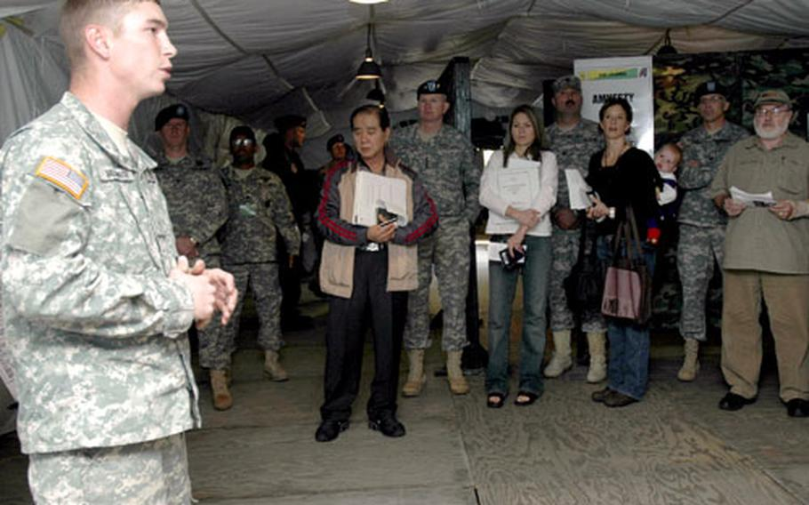 Military civilian workers and dependents listen to a briefing Friday during a semi-annual evacuation training exercise. Among the listeners is Gen. B. B. Bell, commander of U.S. Forces Korea.