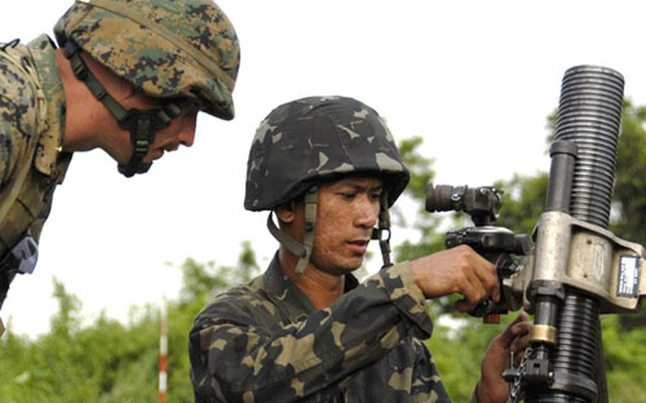 Chief Warrant Officer 2 Joseph Miller, an infantry weapons officer with the 31st Marine Expeditionary Unit, helps a Philippine marine mortarman at the Crow Valley live-fire range in central Luzon, the Philippines.
