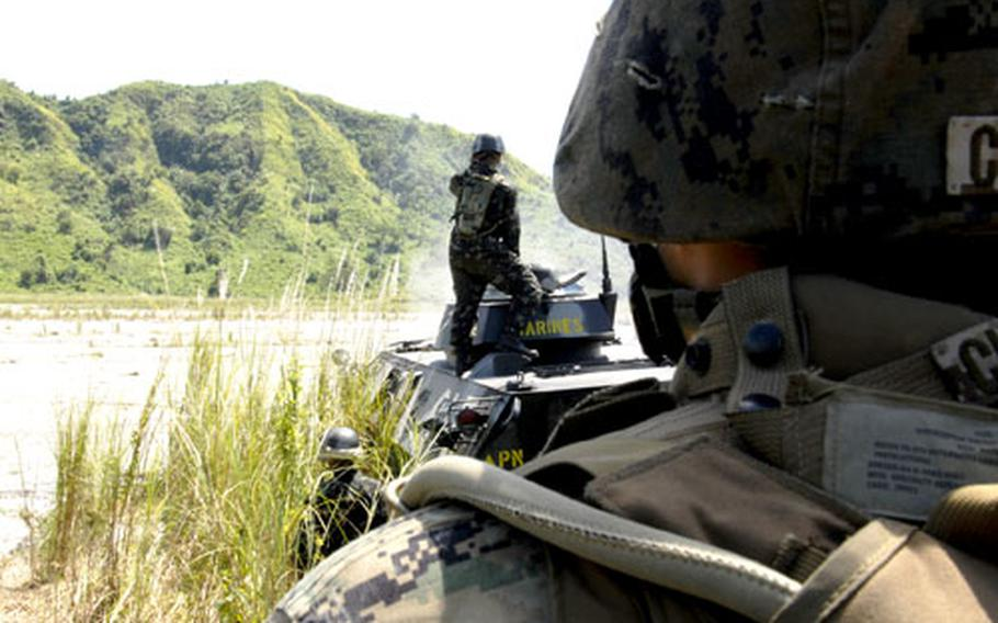 Marine Lance Cpl. Michael Cinko, of the 31st Marine Expeditionary Unit, observes members of the Philippine marine battalion landing team fire the weapons systems of a light armored vehicle in the Crow Valley live-fire range in central Luzon.