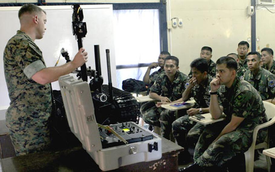 U.S. Marine Staff Sgt. Kevin D. Brown shows a class of Philippine air force explosive ordnance disposal students how to use a robot to handle inert explosives.