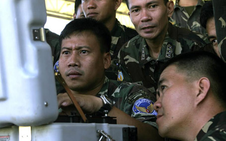 Philippine air force explosive ordnance disposal students watch a monitor linked to a bomb disposal robot at Clark Air Base. The students got an opportunity to try their hands at controlling the robot.