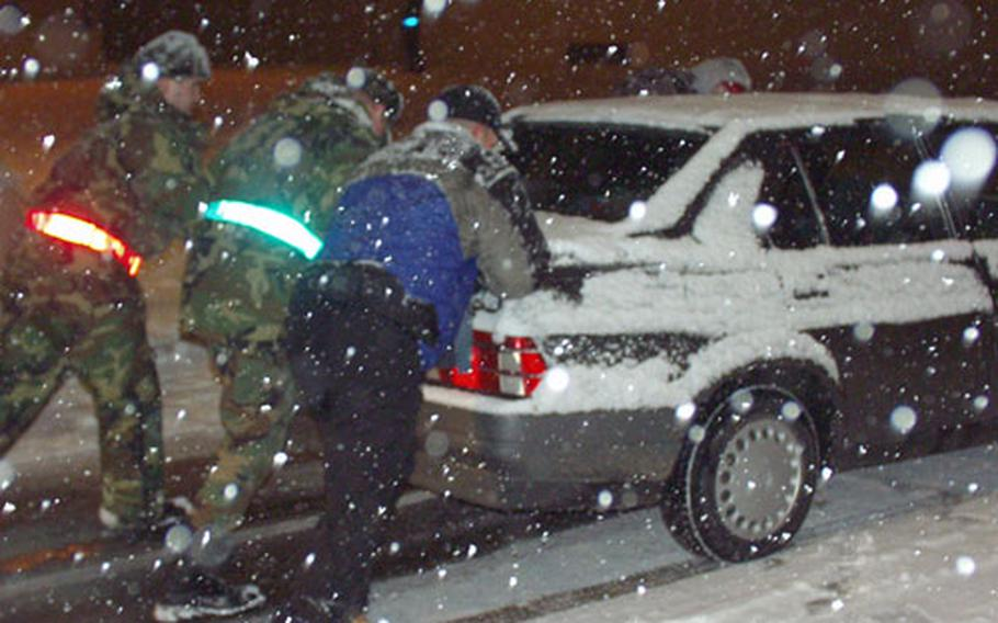 Airmen push a car up the slope and away from the Area 1 gate at Aviano Air Base, Italy, in December 2001.