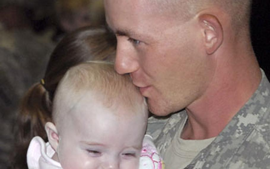 Pfc. Keith Floyd, Company B, 54th Engineer Battalion, kisses his daughter, Kandise, Friday at the Freedom Fitness Facility in Bamberg, Germany. Floyd and other members of the 54th returned after spending a year in Ramadi, Iraq.