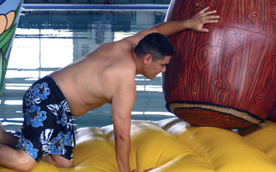 """Sylvester Davila tackles an inflatable obstacle course during Saturday's second annual """"Yokota Couples Fear Factor"""" at the natatorium."""