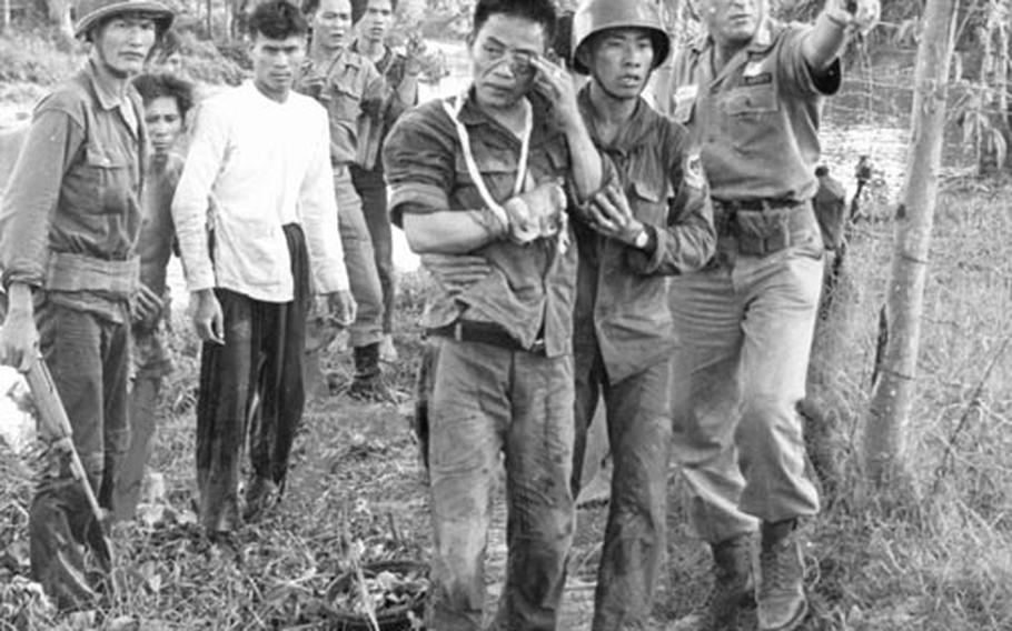 Maj. Robert M. Campbell, right, an American adviser from Fayetteville, N.C., points the way to a helicopter that will bring a wounded Vietnamese ranger, at center, to a hospital. The soldier lost part of his right hand to a Viet Cong booby trap.