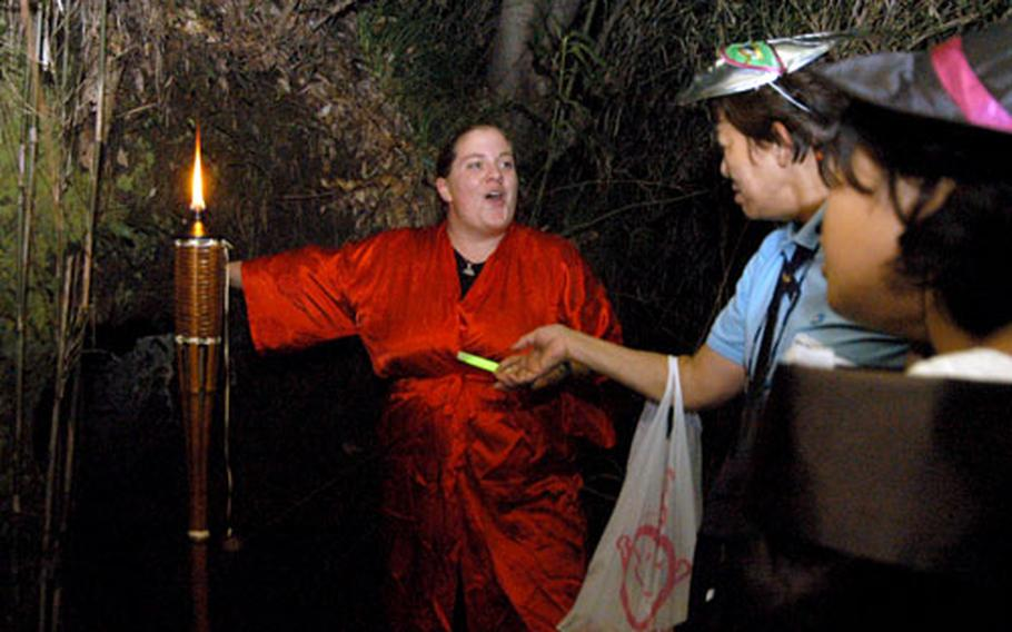"""MWR Aquatics intern Stacey Hosenfeld gestures to a """"yagura,"""" an ancient burial tomb at Ikego's Haunted Forest Saturday."""