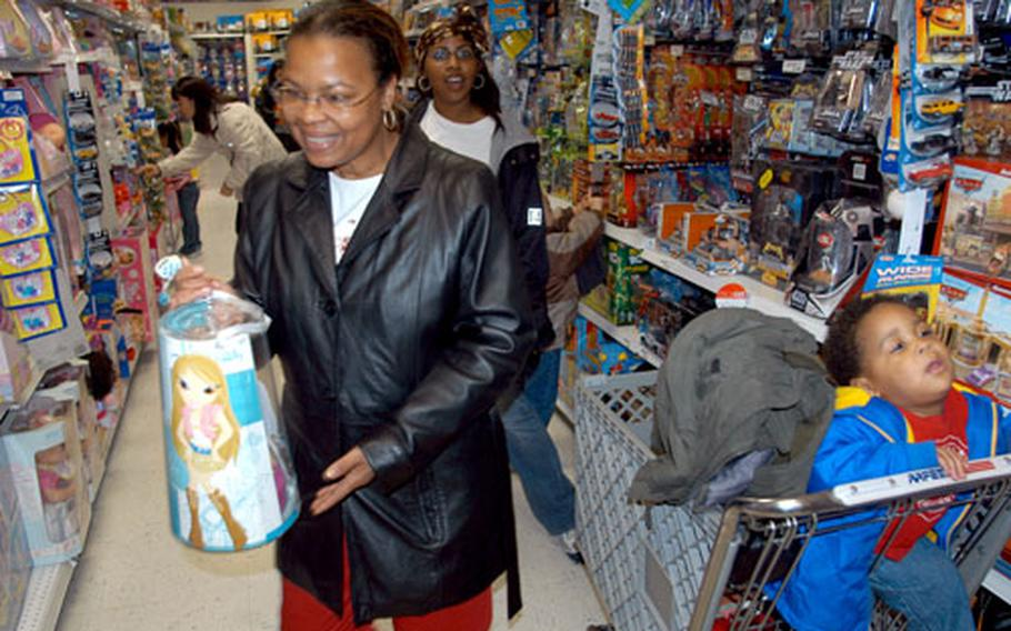 Darlene Kirksey, foreground, and Dana Cooper shop Wednesday at the base exchange at Misawa Air Base, Japan, with Cooper's one-year-old son, Terrance. Military exchanges in the Pacific reported an overall increase of sales during the Thanksgiving holiday weekend from last year.