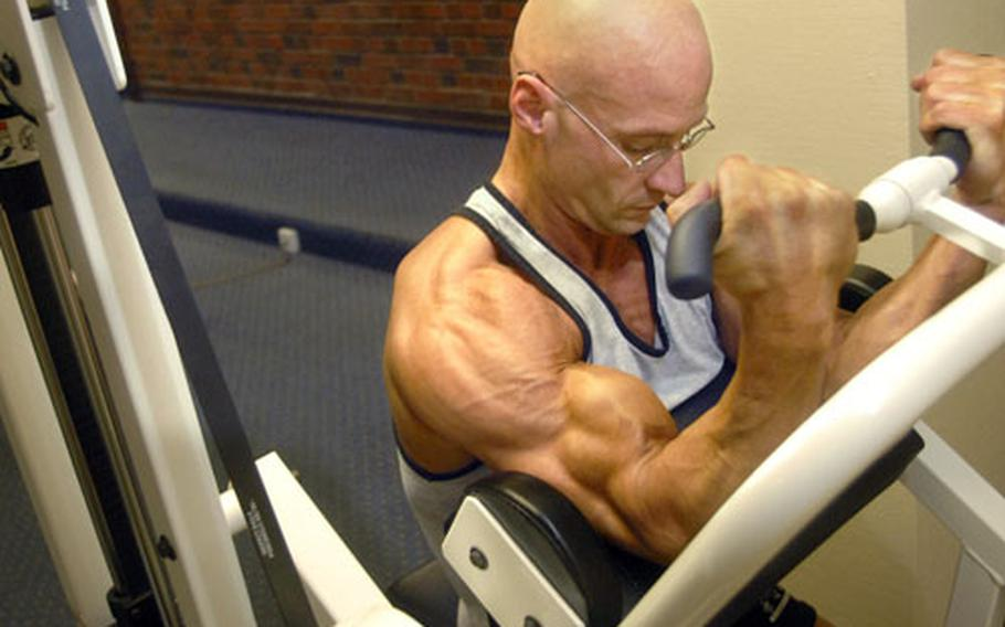 Master Sgt. Troy Saunders works on his back and biceps during a workout session at the base fitness center.