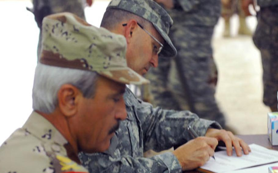 Iraqi Army Maj. Gen. Khorsheed Saleem Hassan Muhammad al-Dosky, left, and U.S. Maj. Gen. Benjamin R. Mixon sign documents during an official transfer of authority ceremony in northern Iraq Monday.