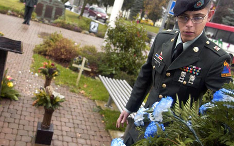 Sgt. Jorge Mora from 4th Battalion, 27th Field Artillery Regiment adjusts a wreath that was used during a memorial ceremony held in honor of Cpl. Jon-Eric Loney in Baumholder, Germany,on Monday.