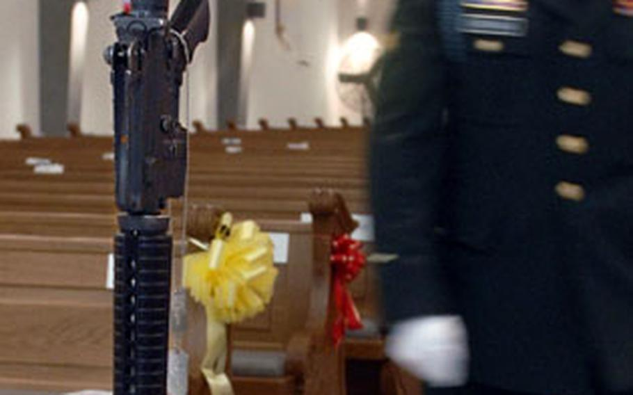 A soldier passes by an upturned rifle honoring Cpl. Jon-Eric Loney at the closure of a memorial ceremony held in the Baumholder chapel on Monday.