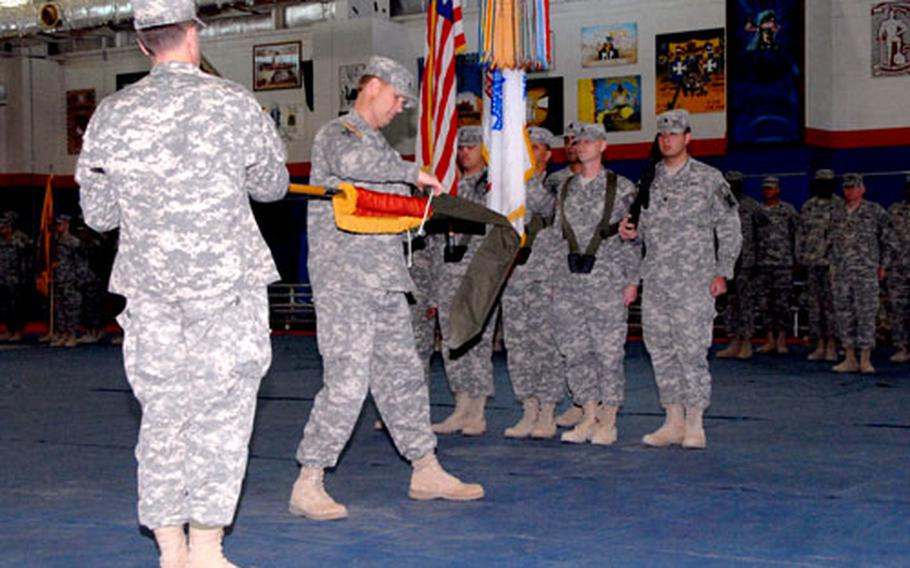 Brig. Gen. Keith Thurgood holds the flag while Sgt. Major Michael Schultz slips it into a cover during the casing of the colors ceremony for the 143rd Transportation Command Monday at Camp Arifjan in Kuwait.