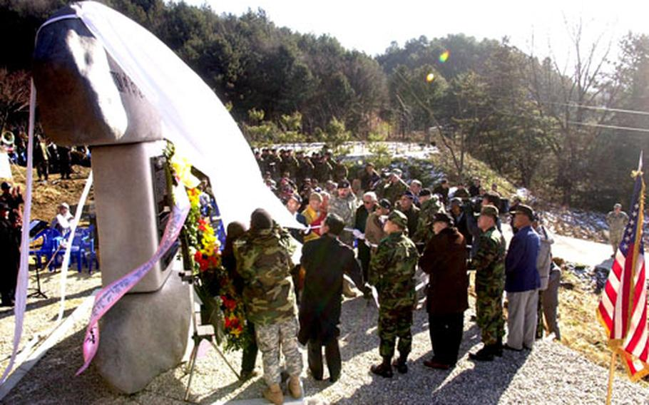 Soldiers and veterans from the U.S. and South Korea unveil the memorial to the 2nd Infantry Division's 1st Battalion, 72nd Armor Regiment, in Chun-an-ri Monday.