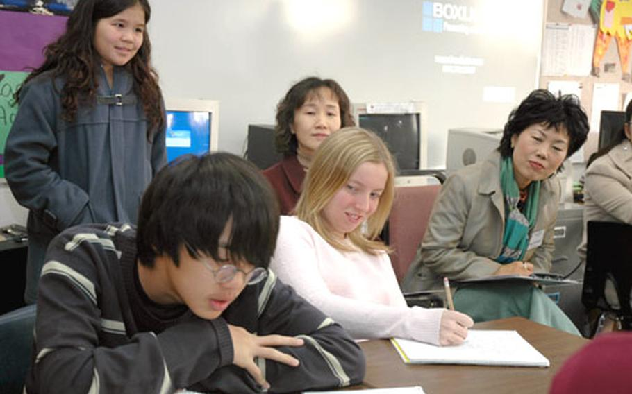 Joseph Park reads his writing assignment aloud in Steve Kennedy's language arts class at Seoul American Middle School on Tuesday morning as visiting South Korean educators look on. Park and Megan Dees, who is seated to his left, are both eighth-graders. The South Korean visitors spent the day at the school observing teaching techniques.