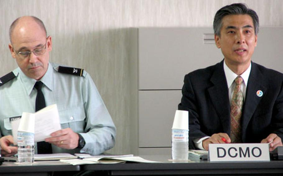 U.S. Army Col. Mark R. Franklin, chief of the Okinawa Area Field Office of U.S. Forces Japan, and Mitsuho Kayashima, Tokyo's director for Crisis Management in Okinawa, co-chair Tuesday's crisis management meeting. The committee was formed in response to confusion at the scene of the crash of a Marine helicopter in the city of Ginowan in August 2004.