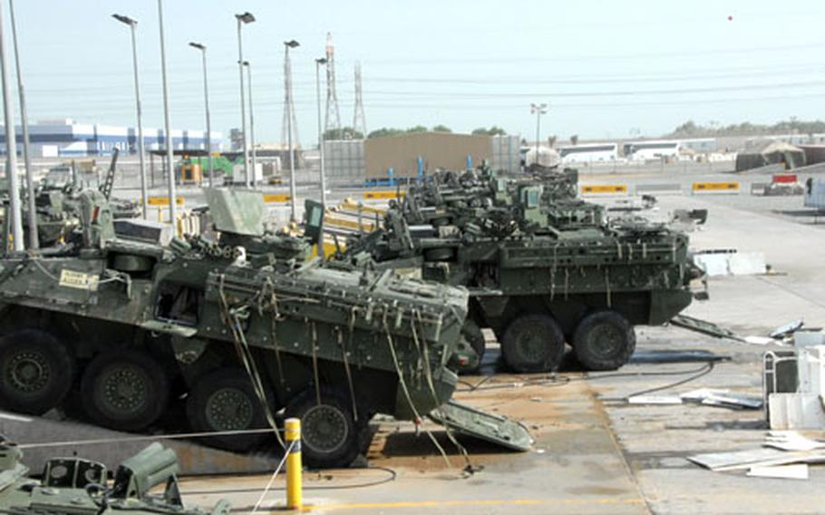 """Some 172nd Strykers wait to be washed before going through customs and onto a ship back to Alaska. The vehicles have to be clean enough to pass a """"pinch test,"""" meaning a customs agent can't pinch any dirt between his fingers during inspection."""