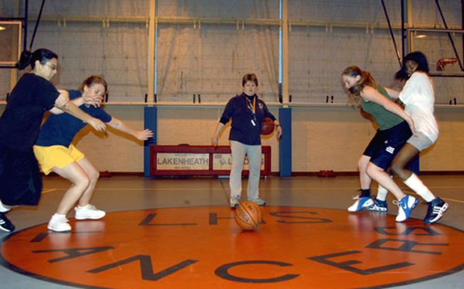 Alconbury girls basketball coach Janis Ready watches as four players practice a boxing-out drill. The Lady Lancers have a handful of returning experienced players.