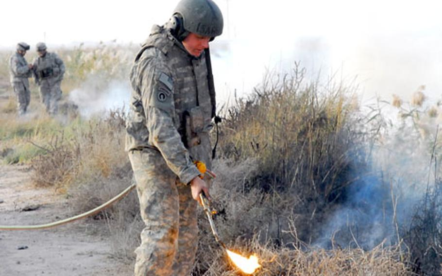Sgt. Jeremy Bell, of the 3rd Platoon of the 15th Engineer Company, uses an acetylene torch to set fire to brush along a roadway in Iraq during a recent route sanitation mission near Muqdadiya in north central Iraq. The missions are intended to remove debris that can be used to hide gunment or explosives along roadways.