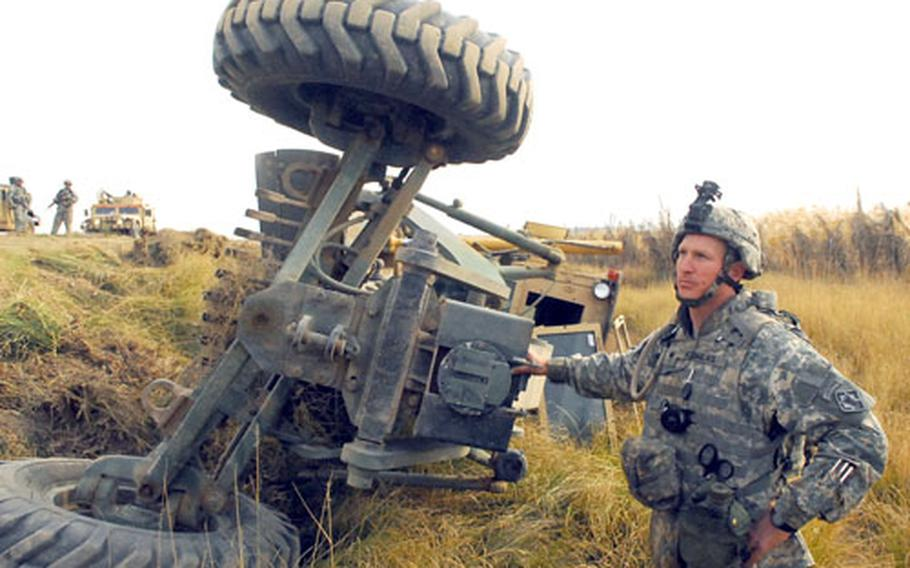 Spc. David Flowers stands beside an upturned road grader moments after he tumbled down an embankment inside the piece of heavy equipment during a route sanitation mission near Muqdadiya.