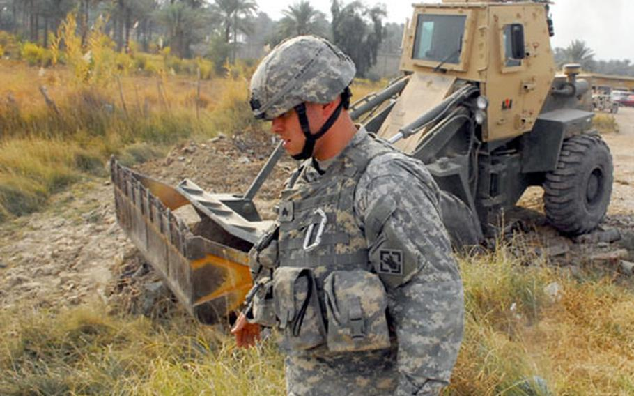 Sgt. Lawrence Davidson, of 3rd Platoon, 15th Engineer Company, directs a bucket loader during a recent route sanitation mission near Muqdadiya.
