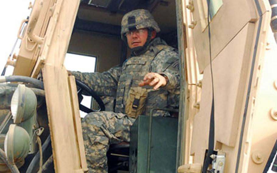 Sgt. David Turner of the 15th Engineer Company sits at the controls of a bucket loader.