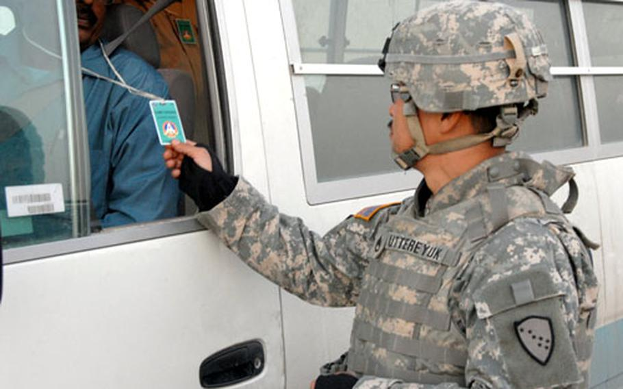 Staff Sgt. Michael Uttereyuk checks the ID of a driver entering Camp Virginia Friday evening.