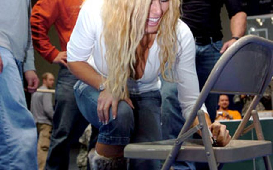 """World Wrestling Entertainment """"Diva"""" Torrie Wilson autographs a chair for the Soldiers of the 3rd Brigade Combat Team, 1st Cavalry Division, during a visit to Forward Operating Base Warhorse."""