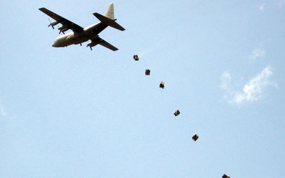 Flood-relief supplies are dropped out of a C-130 aircraft flying over the Dadaab region of Kenya.