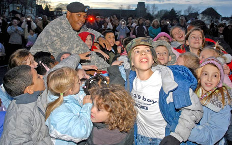 Children of the Friedberg, Germany, community help rear detachment commander Maj. Tony Perry flip the switch to light the community Christmas tree in front of 1st Brigade headquarters on Ray Barracks earlier this month. Many of the children have a parent deployed to Iraq.