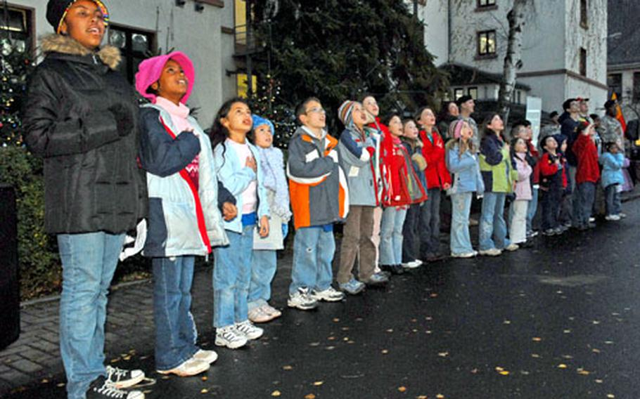 Scouts from the Friedberg, Germany, community recite the Pledge of Allegiance outside 1st Brigade headquarters on Ray Barracks, before the lighting of the community Christmas tree. A moment of silence for the fallen was also observed. The trees behind the children are decorated with bulbs with the names of the fallen and every 1st Brigade soldier deployed to Iraq.