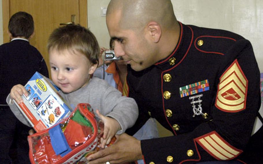 Gunnery Sgt. Carlos Flores hands 2-year-old Salvatore a few gifts Tuesday as part of the Toys for Toys holiday campaign. Marines and sailors from the Naples, Italy, area collected thousands and thousands of toys from donors, which are being distributed to 28 area charities, schools and churches for underprivileged children.