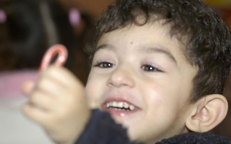 Antonio, 3, beams after receiving a candy cane.