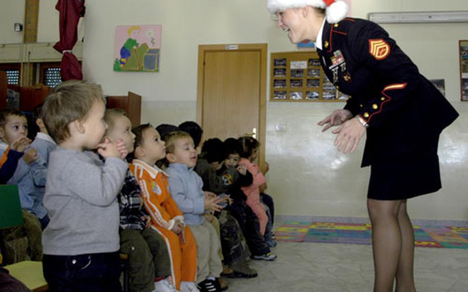 """Marine Staff Sgt. Stacie Crowther sings """"Oh Happy Day"""" with children of the Stelle Dei Angeli (Stars of the Angel) day care and school."""