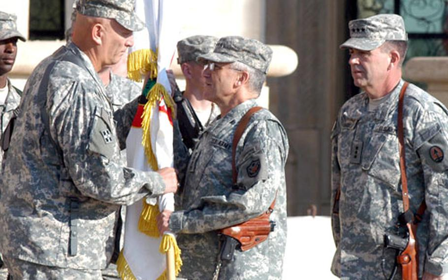 Gen. George Casey, center, the commander of all U.S. forces in Iraq, hands the flag of Multi-National Corps-Iraq to Lt. Gen. Ray Odierno, commander of the U.S. Army's III Corps, during a transfer of authority ceremony Thursday at Camp Victory in Baghdad. At right is Lt. Gen. Peter W. Chiarelli, the outgoing commander of MNC.
